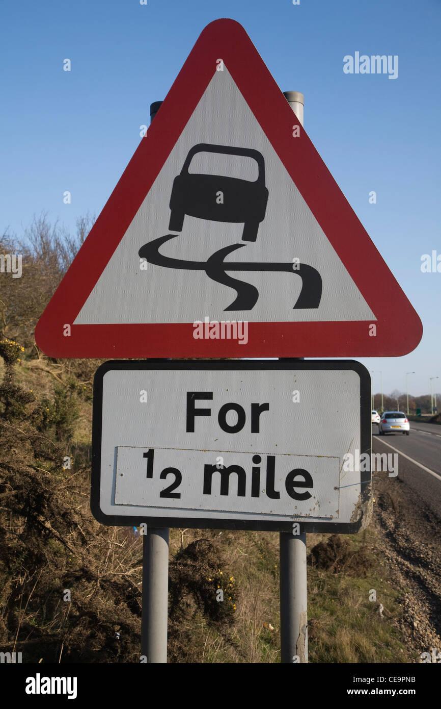 Señal de tráfico triangular del código de carreteras resbaladizas camino por media milla Imagen De Stock
