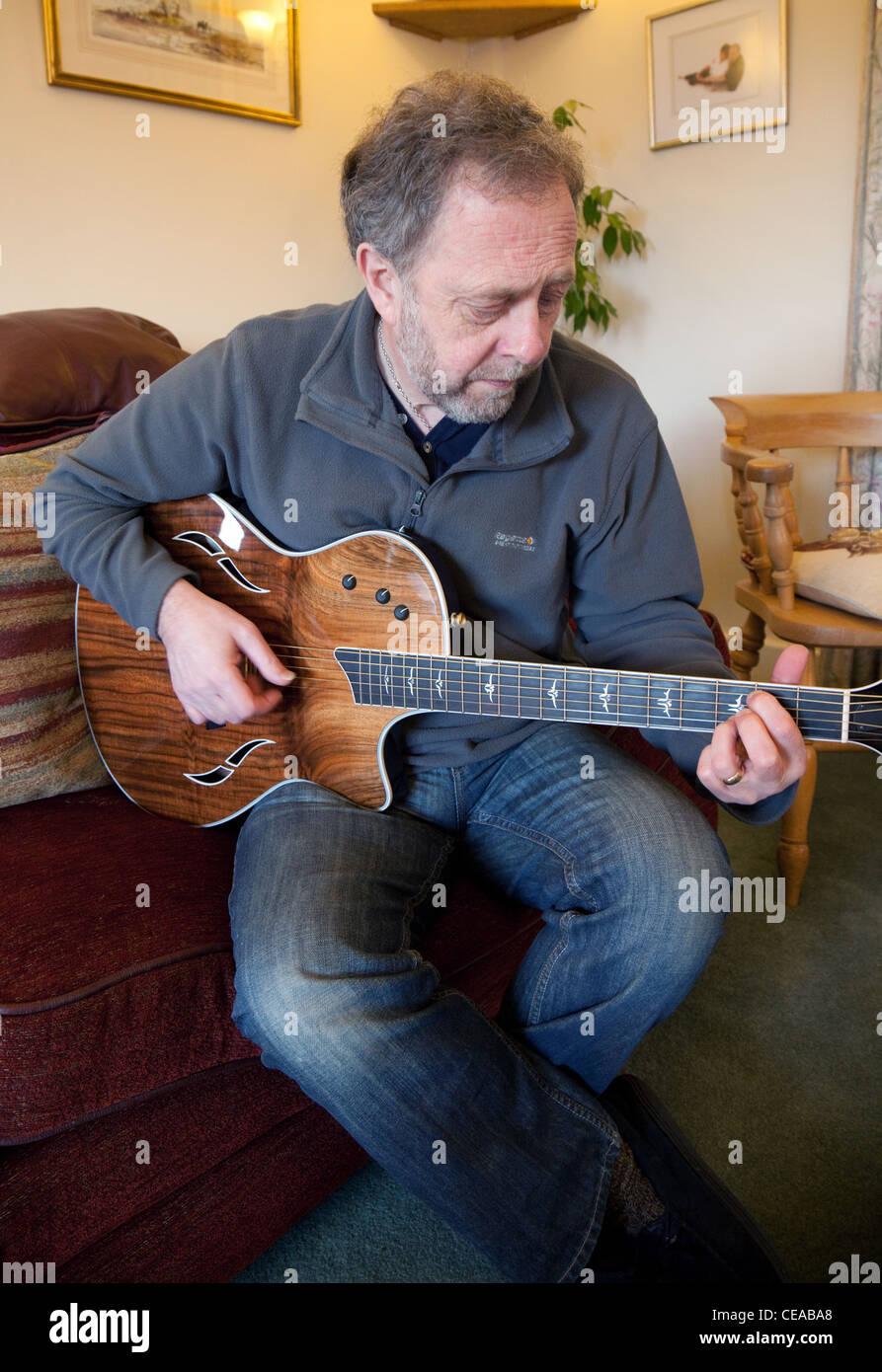 Un hombre de mediana edad Taylor tocando una guitarra acústica, UK Imagen De Stock