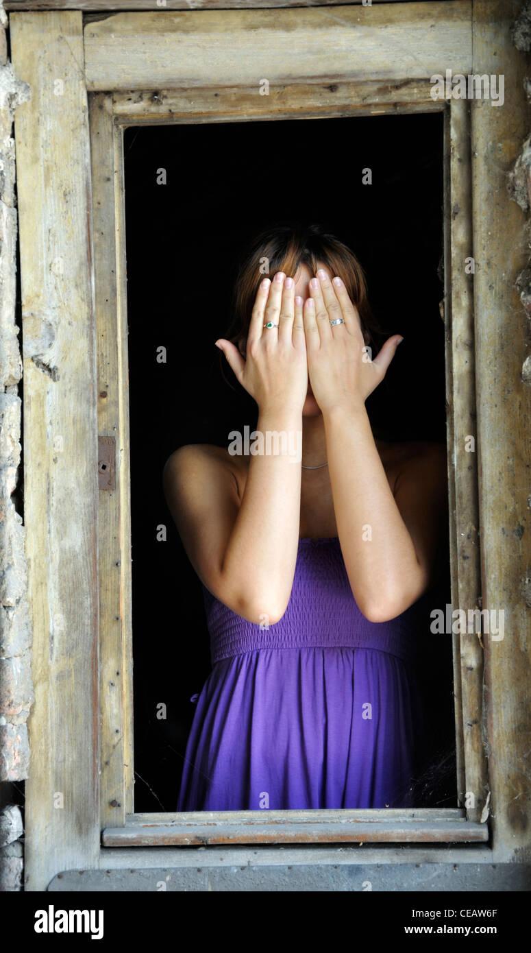 Retrato de una joven mujer de pie en el marco de la ventana que cubre cara Imagen De Stock
