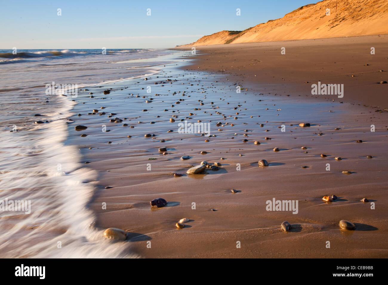 Ola de lava sobre pequeñas rocas en Playa Marconi, Wellfleet Imagen De Stock