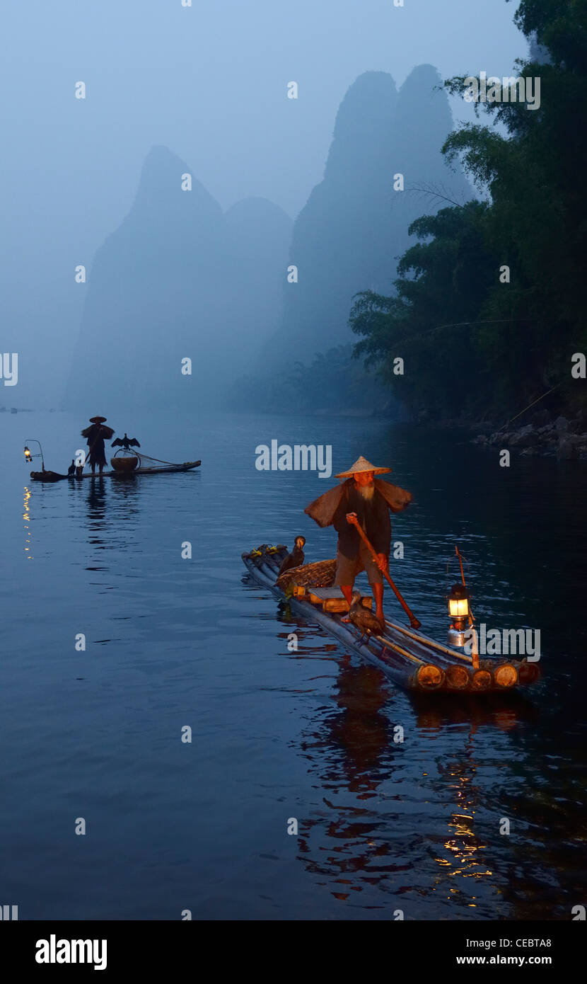 Temprano en la mañana dos pescadores de cormoranes en balsas de bambú en Li o río Lijiang cerca Xingpingzhen Yangshuo, Guangxi, Guilin, China Foto de stock