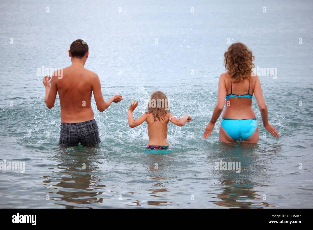 Familia Feliz con Little Girl salpican agua manos de pie sobre la correa en el mar, de pie atrás Imagen De Stock