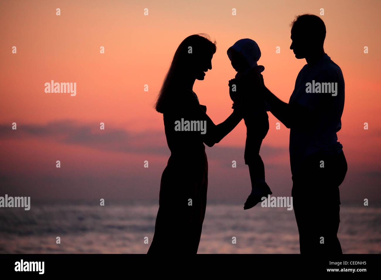 Las siluetas de los padres con el niño en manos contra el declive del mar Imagen De Stock