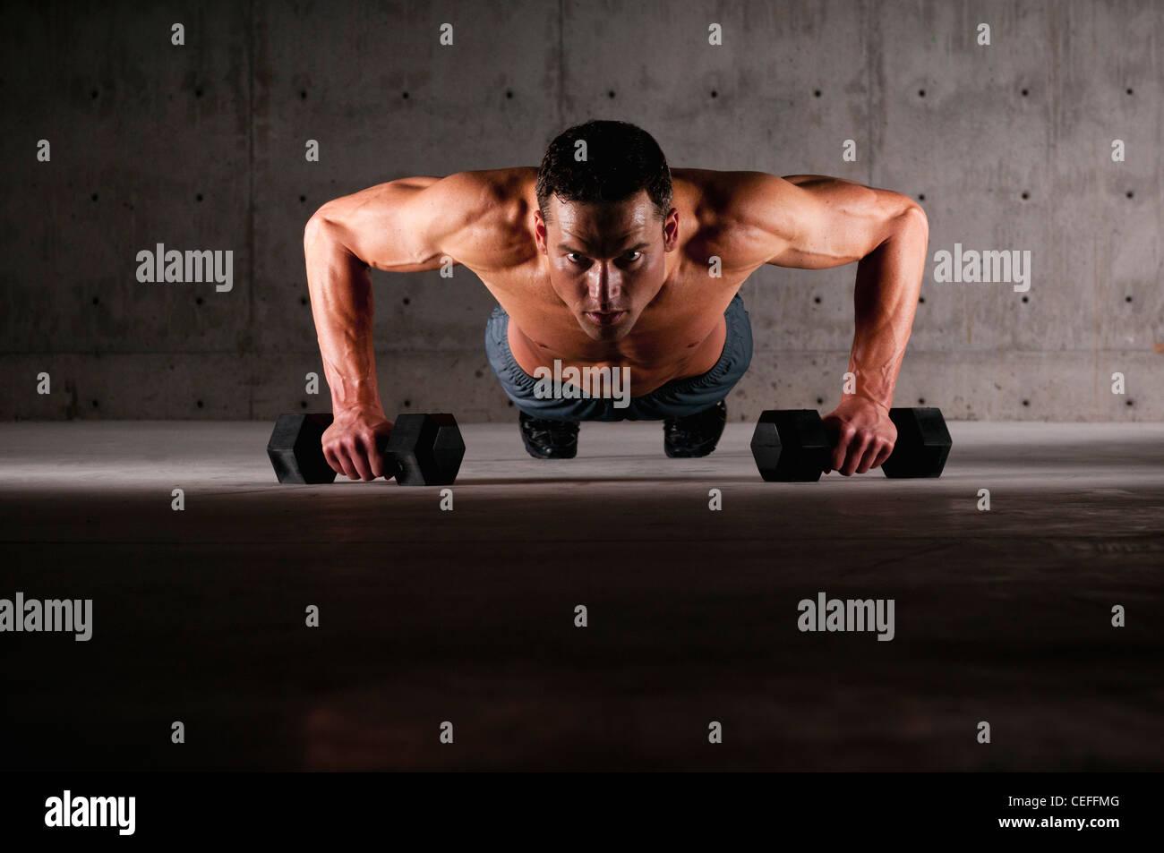 Atleta haciendo flexiones sobre pesos Imagen De Stock