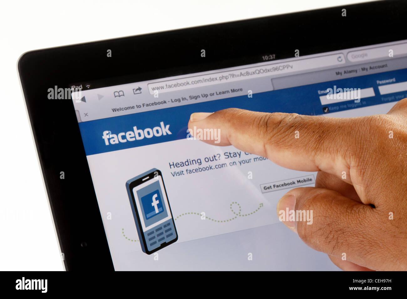 Sitio facebook en Apple iPad2 y señalar con el dedo Imagen De Stock