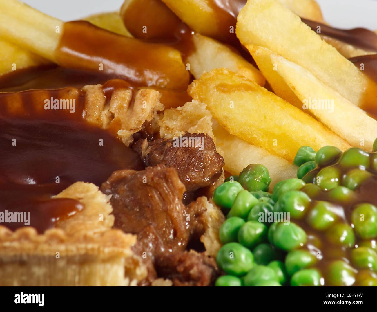 Cerca de torta de carne y papas fritas con guisantes y salsa. Un plato tradicional británico Imagen De Stock