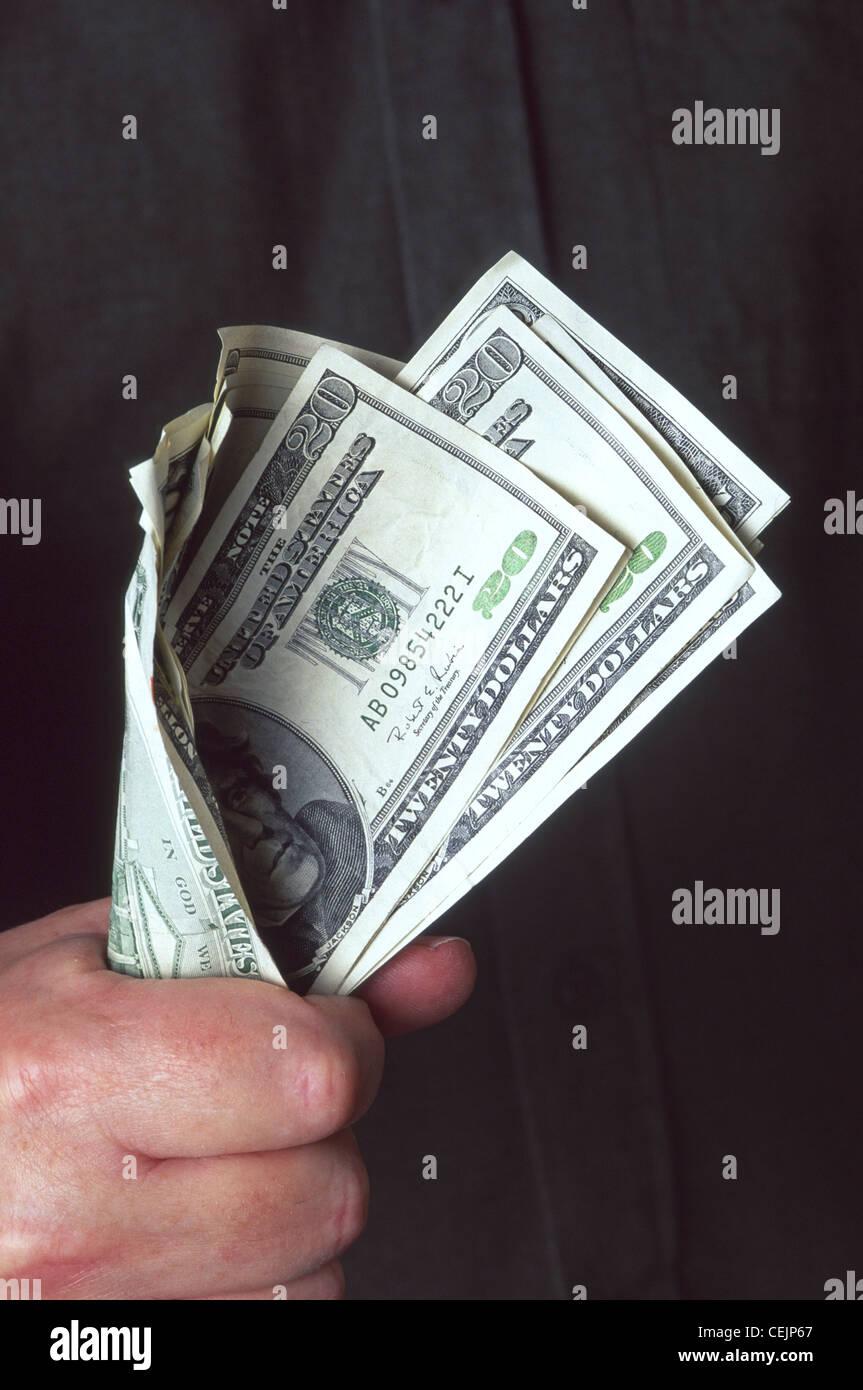 Concepto tipo imagen cerca de efectivo en mano o el puñado de dólares con greenbacks celebrada en un mans Imagen De Stock
