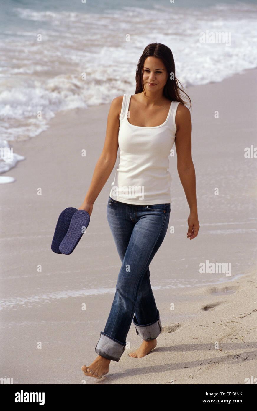 Mujer morena de largo cabello top chaleco vestidas de blanco y azul oscuro  pantalones vaqueros enrollada c6dc5e39ede8