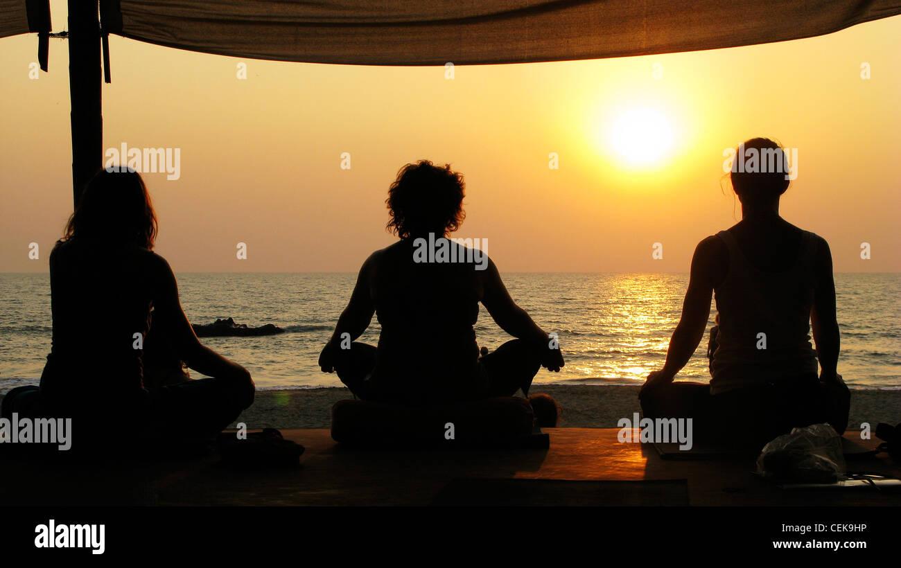 Yoga y meditación al atardecer en la playa de Patnem Palolem, Goa (por la playa), India Foto de stock