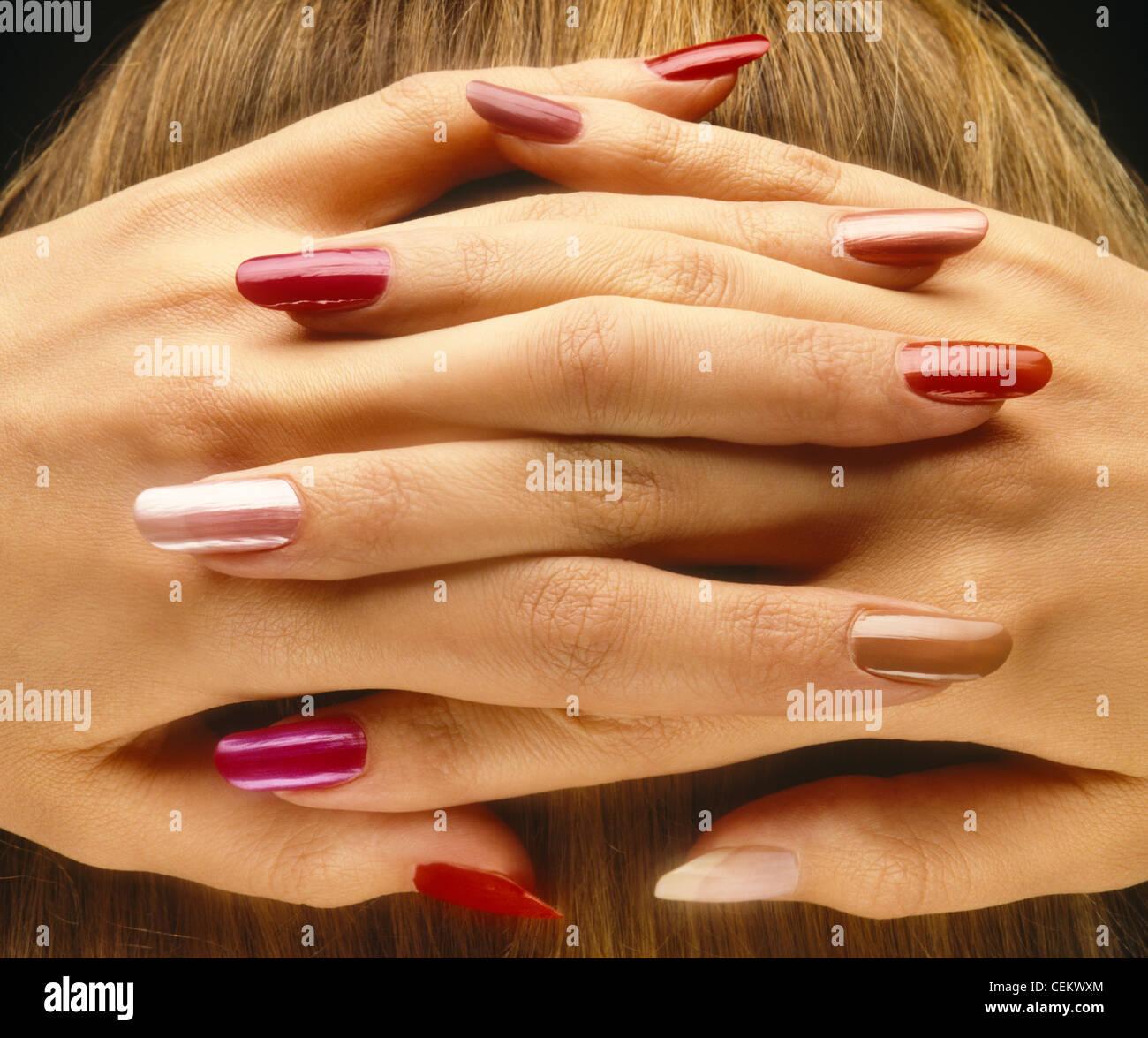 Hembra con sus dedos entrelazados detrás de su cabeza con diferentes colores de laca de uñas en cada dedo Imagen De Stock
