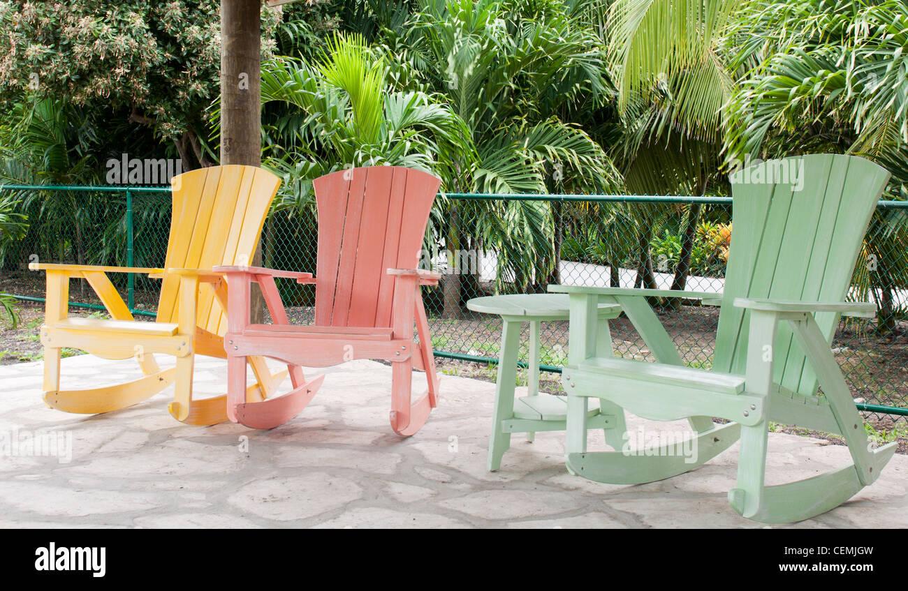 05980e403 Colorido mecedoras de madera en un pórtico (ajuste en un complejo tropical)  Imagen De