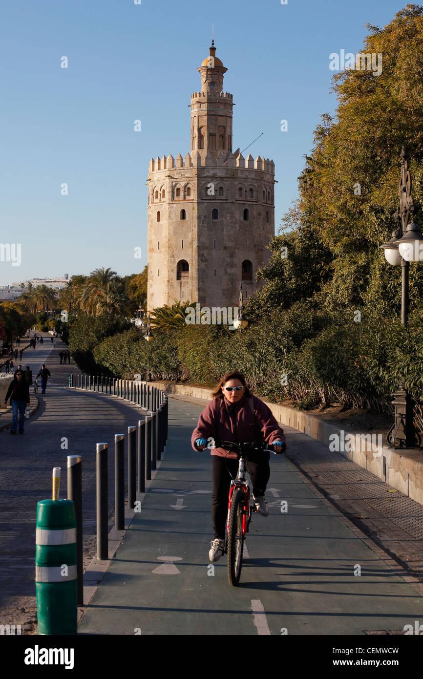 Mujer en bicicleta cerca de la Torre del Oro (Torre del Oro) en Sevilla, España. Imagen De Stock