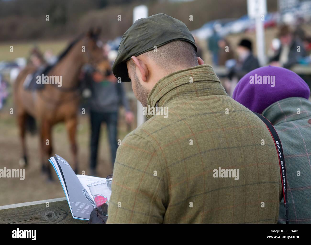 Un jugador lee la tarjeta antes de la carrera de Shepherd Neame Mens carrera abierta al sureste de Hunts Club carreras Imagen De Stock