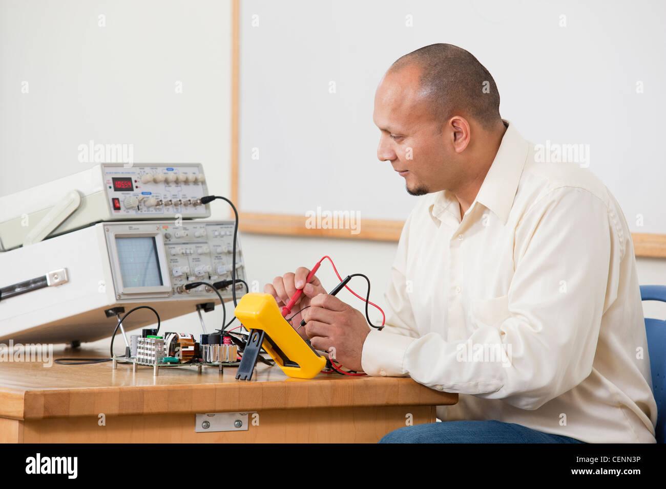 Hispanic ingeniería utilizando las sondas del multímetro para medir características del circuito Imagen De Stock