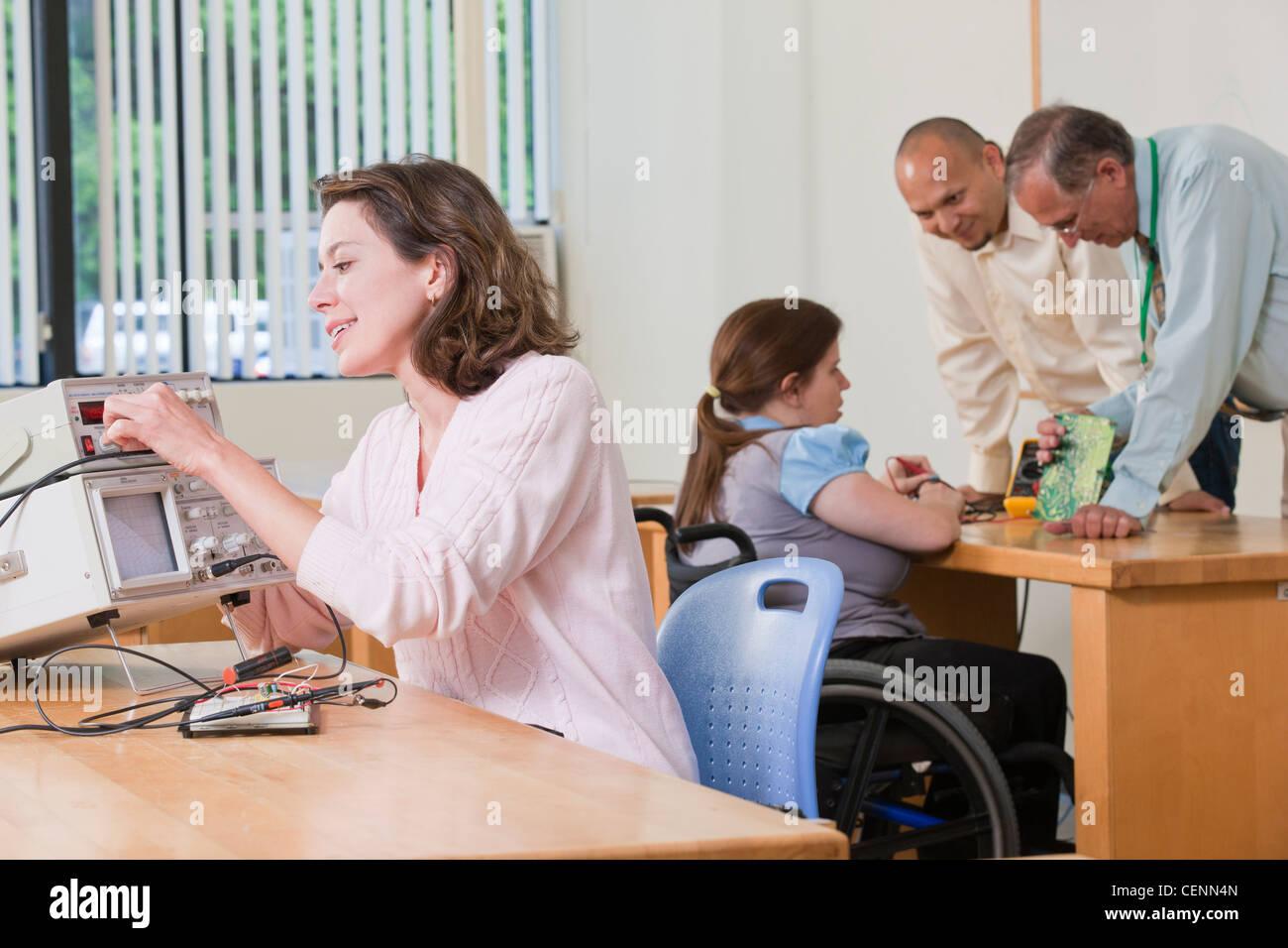 Generador de funciones de conexión del estudiante mientras el profesor está demostrando un circuito impreso Imagen De Stock