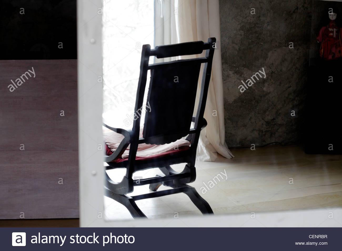 Comodidad silla mecedora delante de una gran ventana con vistas a un paisaje nevado bajo Imagen De Stock