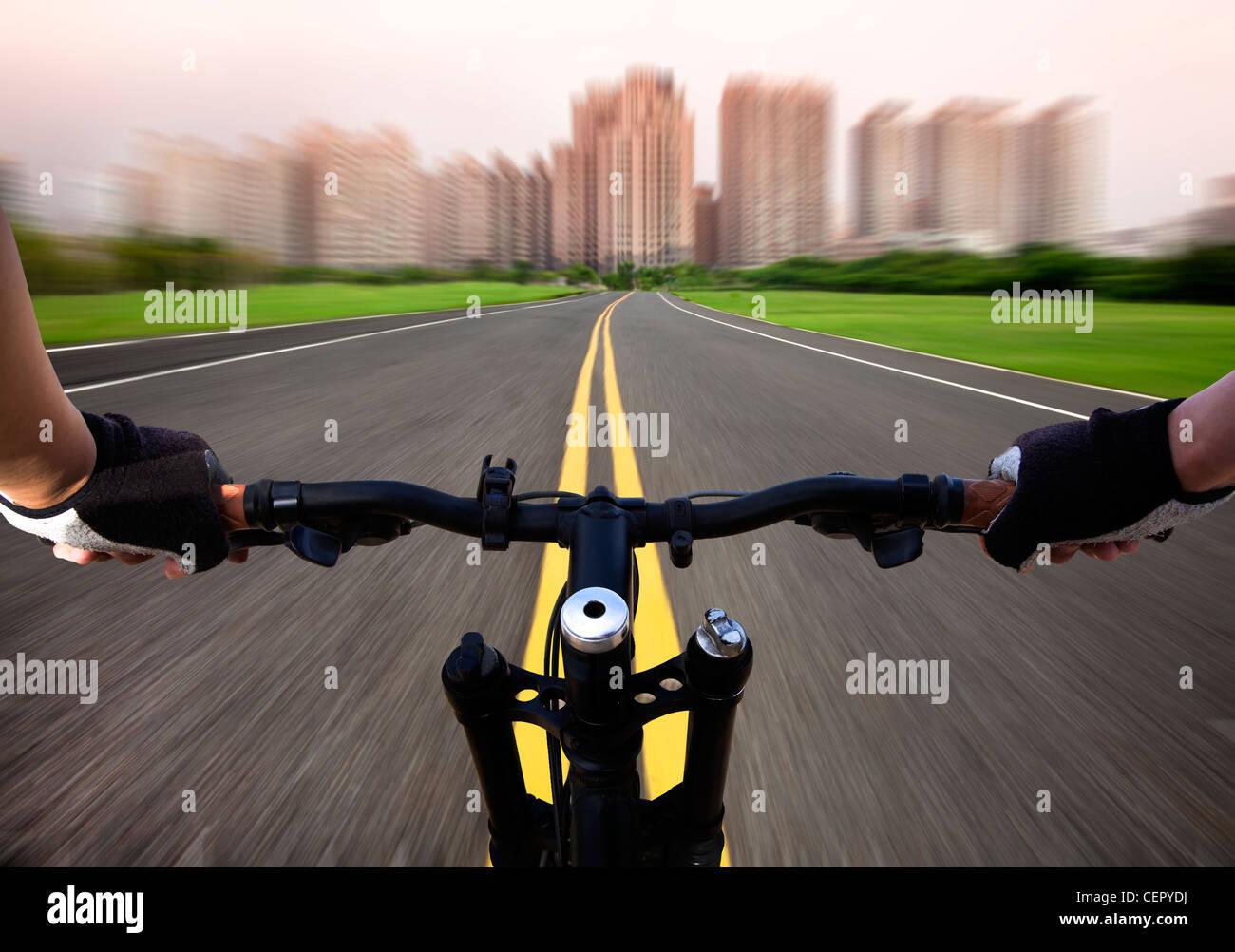Jinete de bicicleta y equitación de alta velocidad a la ciudad en la carretera Imagen De Stock
