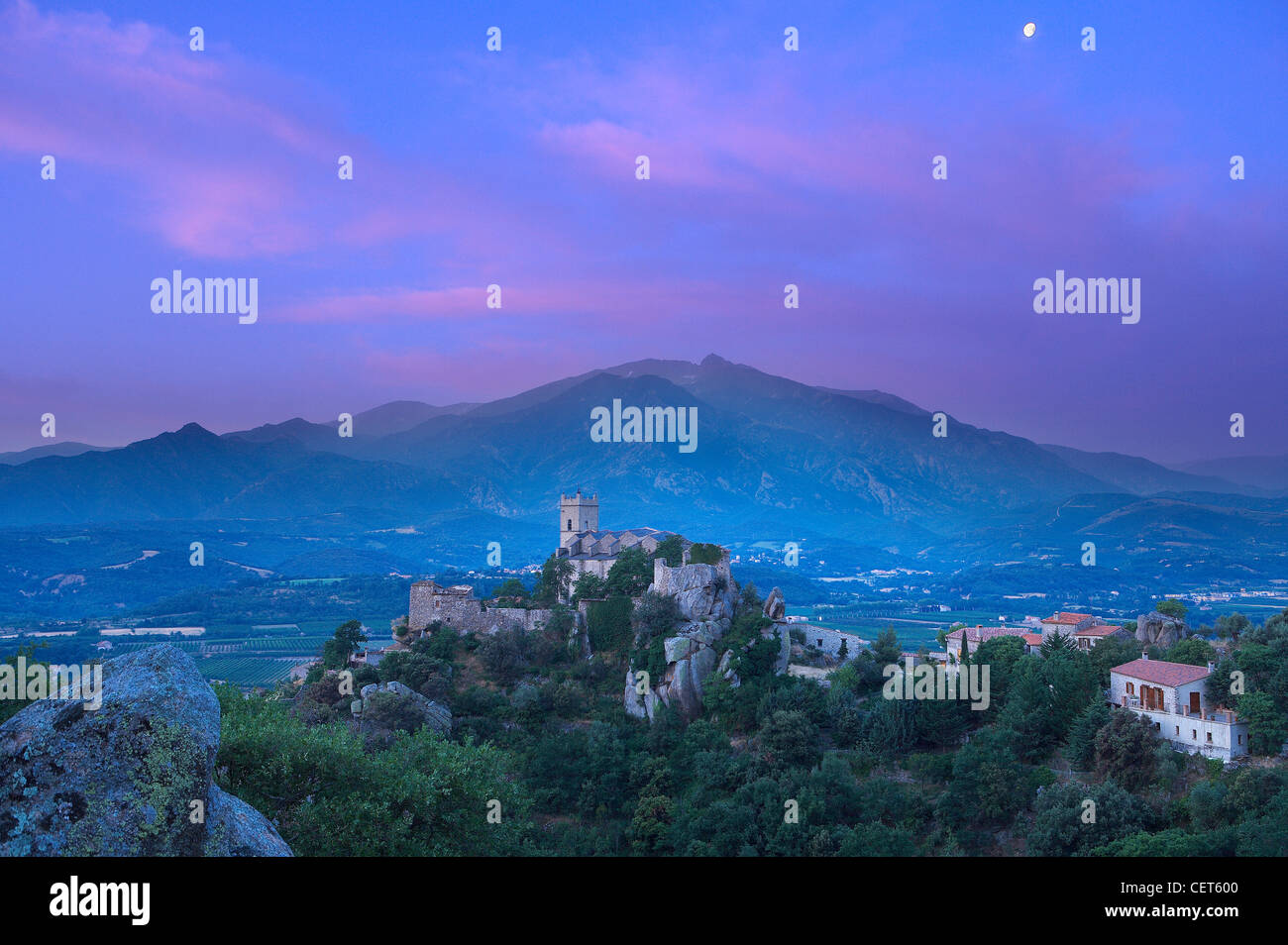 La aldea de eus encaramado en lo alto de una colina con el Pic de Canigou, más allá de los Pirineos, Languedoc Imagen De Stock