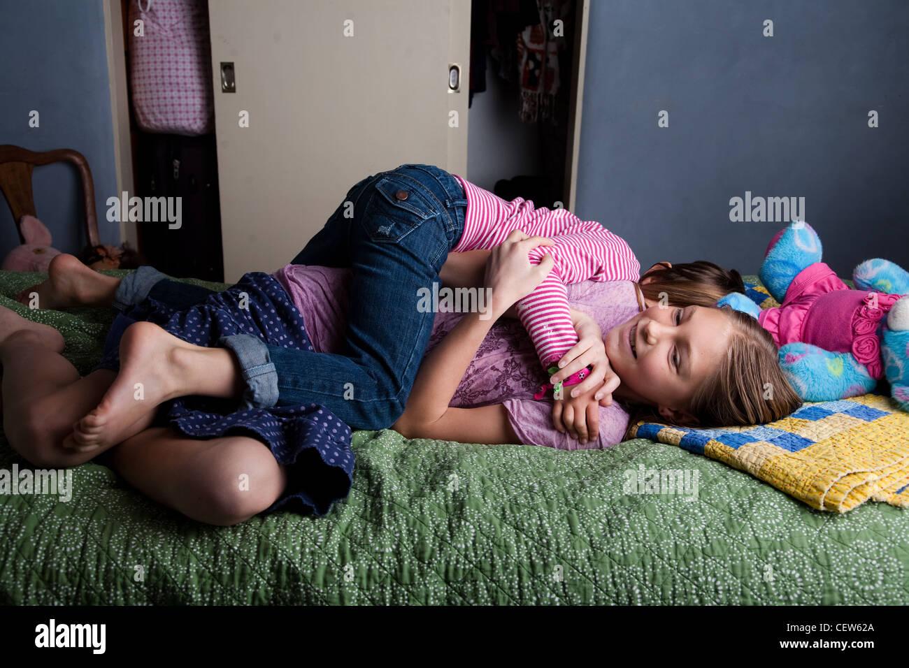 Dos niñas luchando sobre la cama Foto de stock