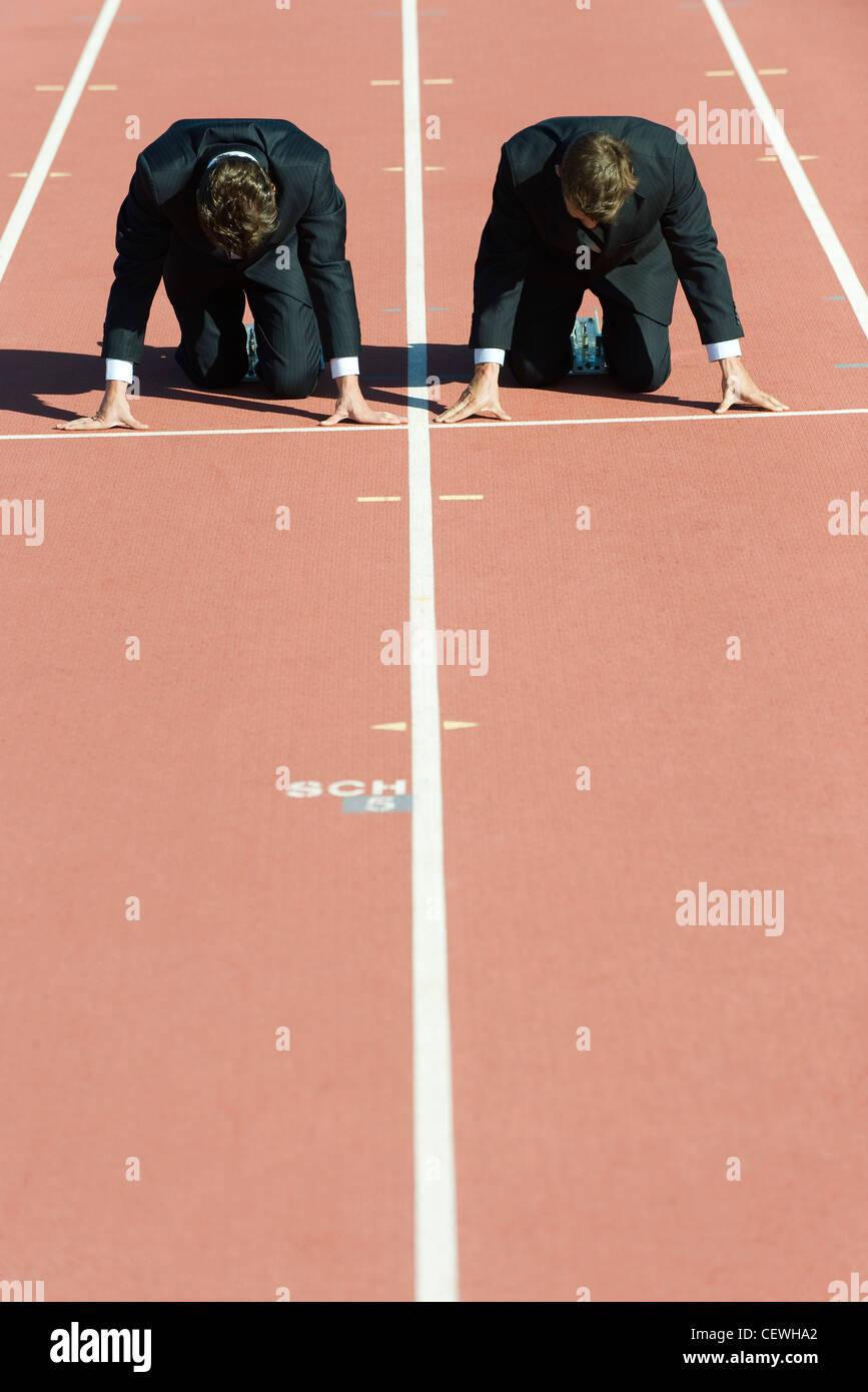 Los empresarios se puso en cuclillas en posición de partida en la pista de atletismo Imagen De Stock