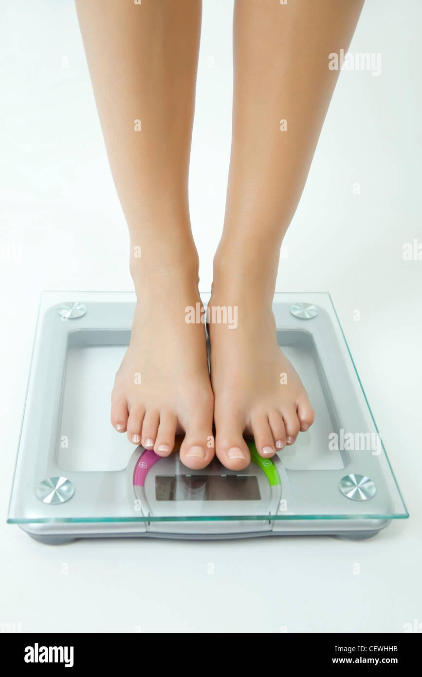 Mujer pesando ella misma en una balanza de baño, bajo la sección Imagen De Stock