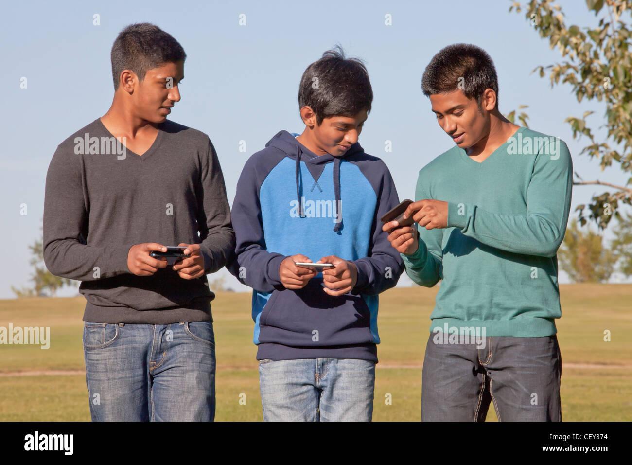 Hermanos texting y caminar a través de un parque; en Edmonton, Alberta, Canadá Foto de stock