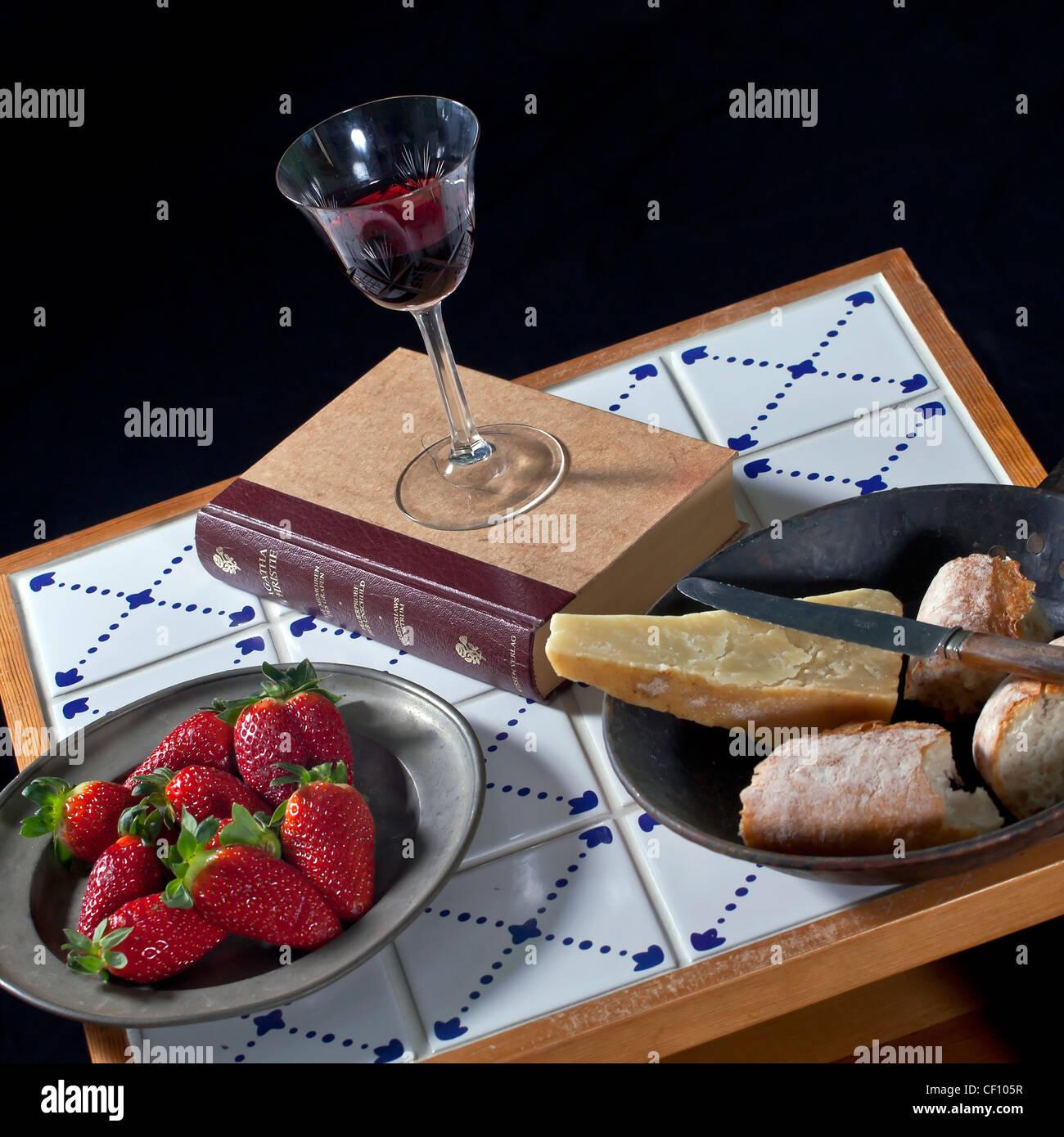 Acogedor snack: un libro sobre una mesa hecha de antiguos azulejos con vino tinto, fresas, queso y pan Imagen De Stock