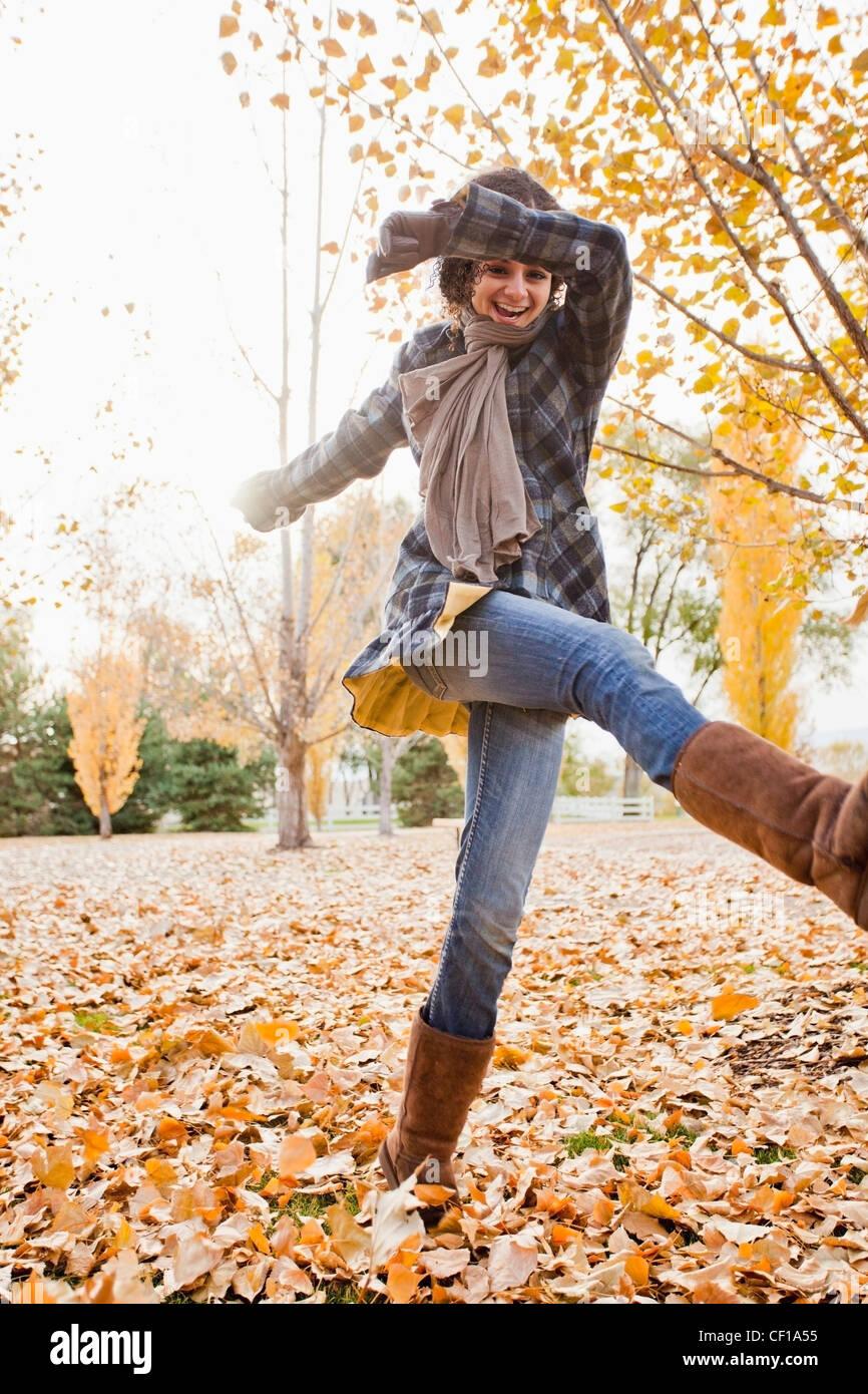 Mujer caucásica jugando en hojas de otoño Foto de stock