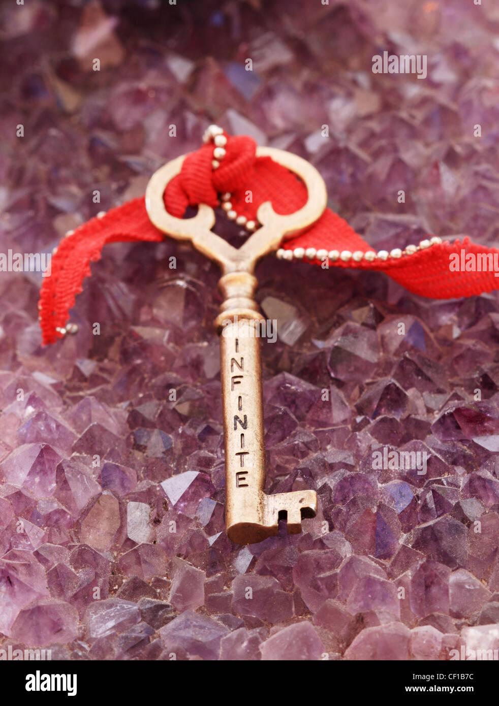 Infinito escrito en una clave antigua de bronce sentado en cristales de amatista Foto de stock