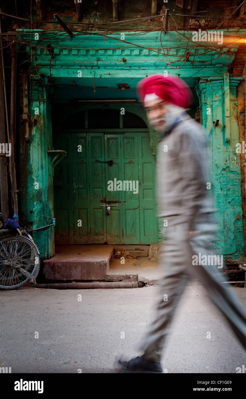 Rojo indio turbaned hombre Sikh ante la puerta verde en el casco antiguo de la ciudad de Amritsar Foto de stock