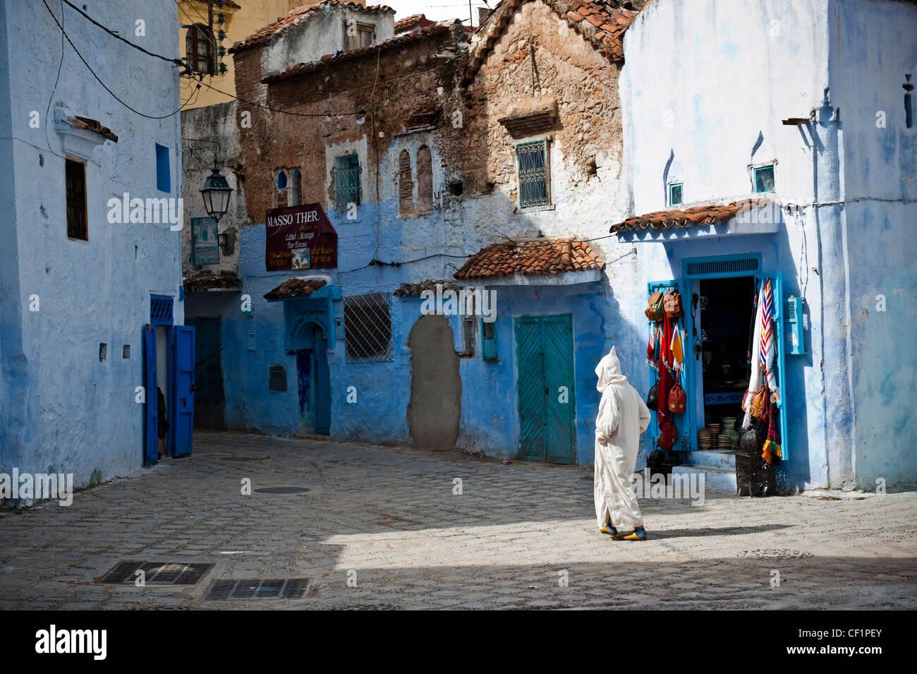 Hombre musulmán caminando en la pared azul de la antigua medina de Chefchaouen, Marruecos Foto de stock