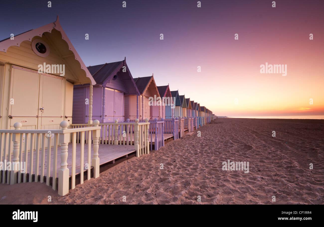Amanecer sobre nuevas cabañas de playa en la isla de Mersea. Foto de stock
