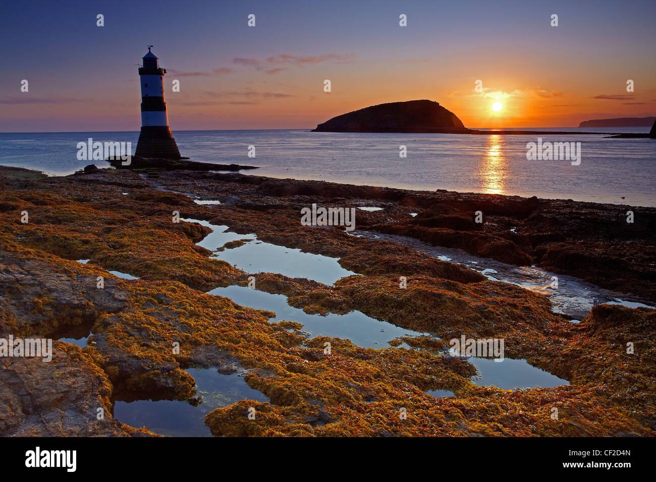 Penmon Faro, también conocido como faro de Menai, en la entrada norte del estrecho de Menai Isla Puffin opuesto al amanecer. Foto de stock