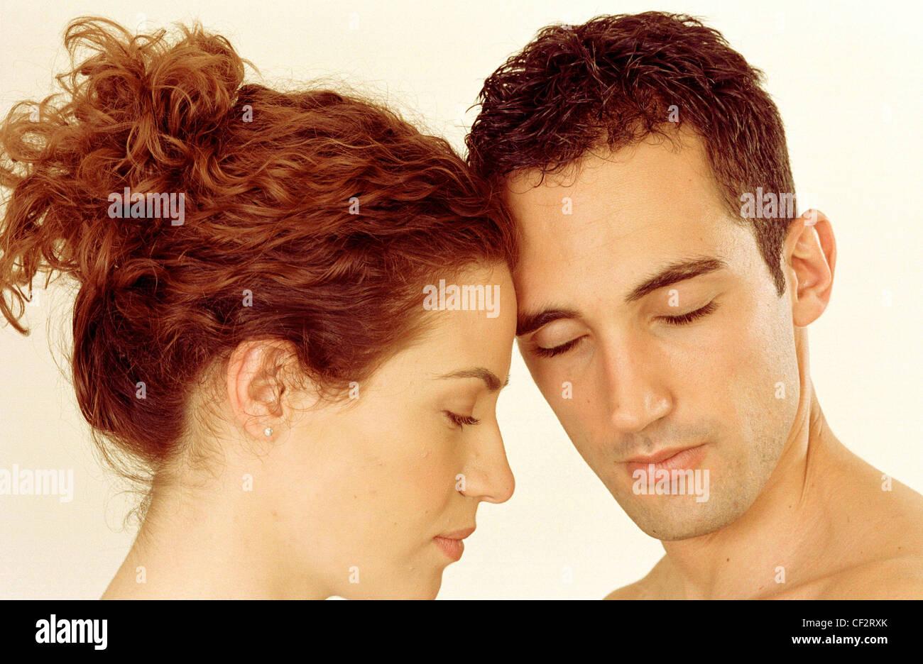 Perfil de mujer de pelo rojo rizado izquierdo fuera de cara a la izquierda  macho corto pelo castaño gira a cámara inclinándose en tocar frentes 9e6c09121f3