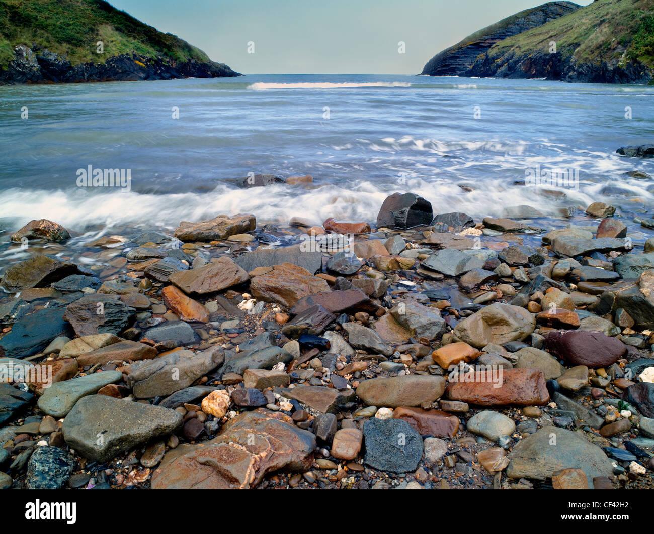 Vista a través de guijarro sembrado Ceibwr Bay hacia el Mar de Irlanda. Foto de stock