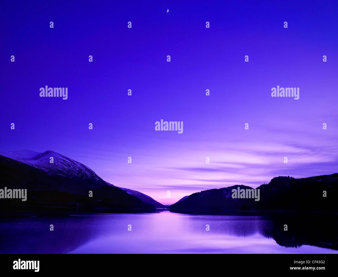Una Luna creciente se eleva por encima de Thirlmere como oscuridad en el Lake District. Imagen De Stock