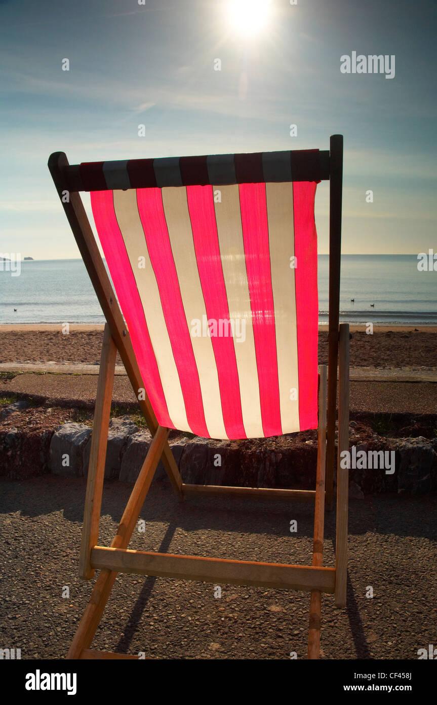 Retroiluminación stripey tumbona en la playa en Paignton en la Riviera Inglesa en la costa de Devon. Imagen De Stock