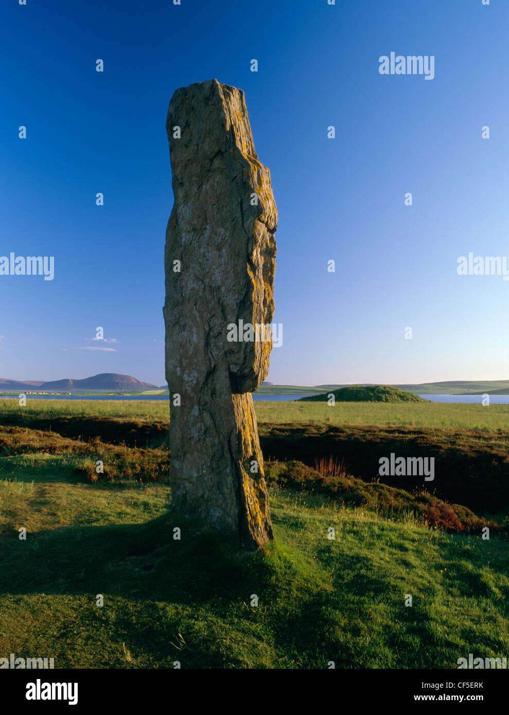 Mirando desde la estatura losa occidental del anillo de Brodgar Stone Circle, a través del lago de Stenness Ward Hill en la isla o Foto de stock