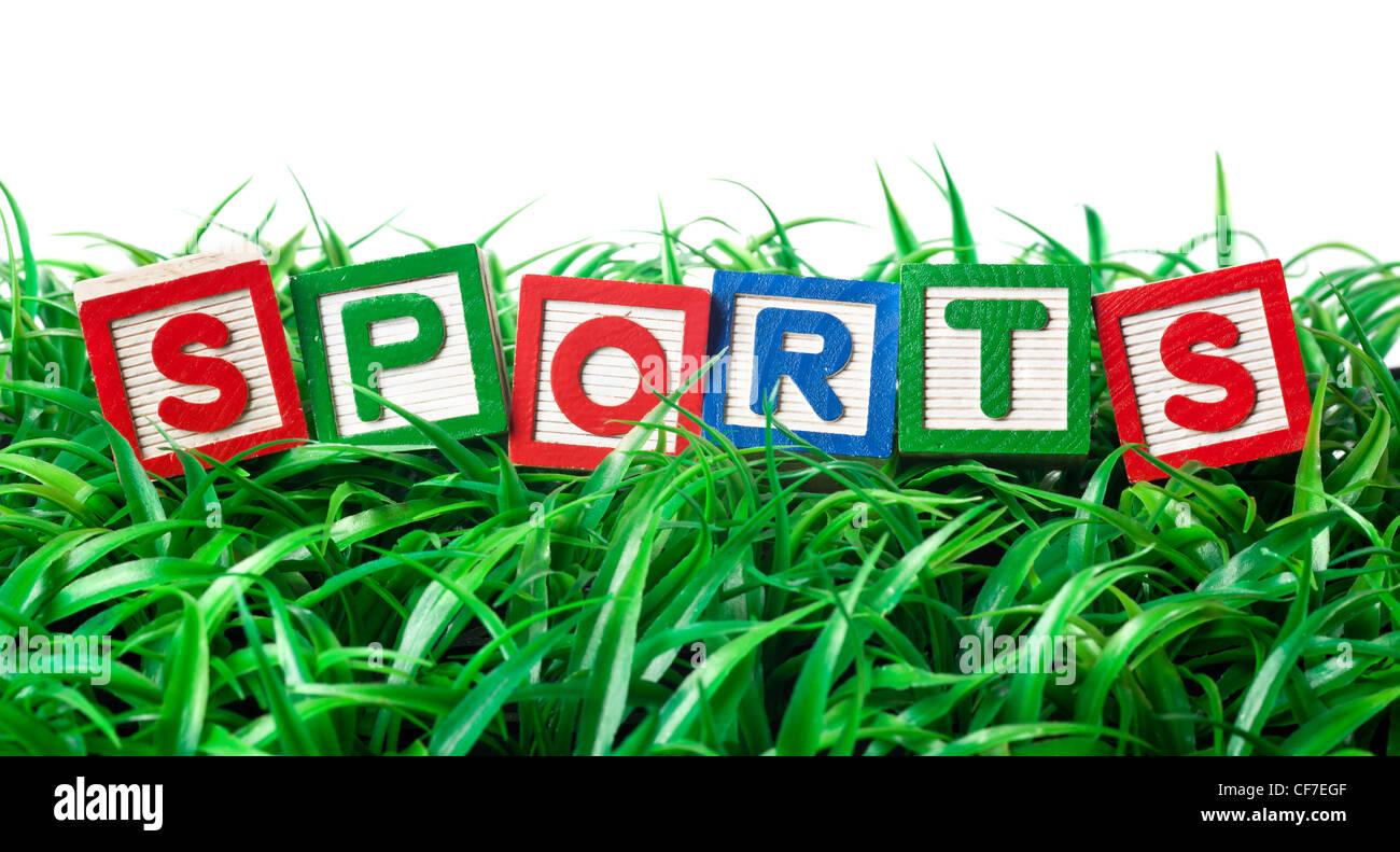 Alfabeto formando bloques de deportes en un parche de hierba Imagen De Stock