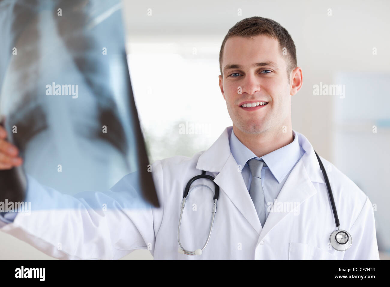 Sonriente joven doctor mirando x-ray Imagen De Stock