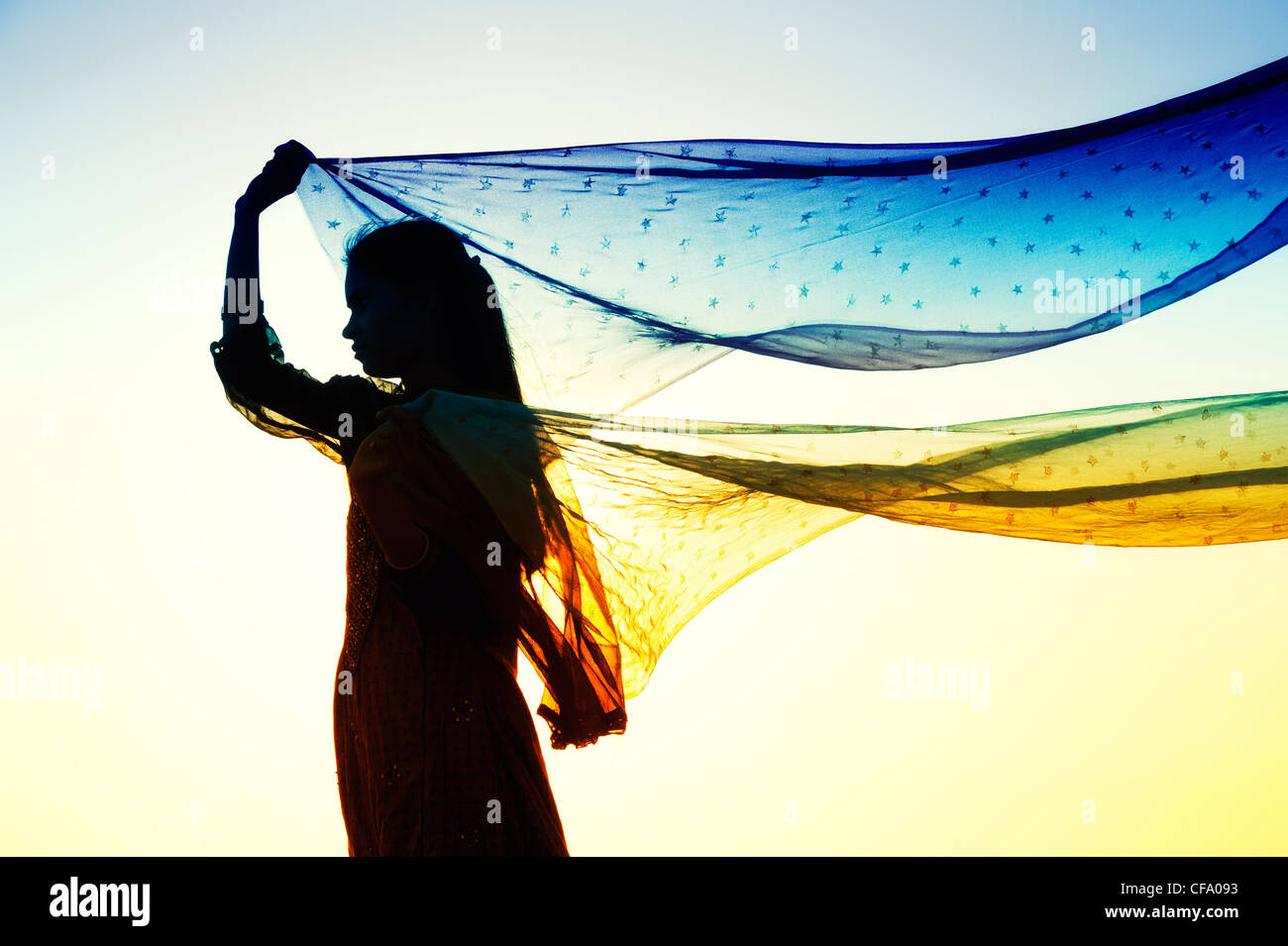 Niña India con estrellas velos estampados en el viento. Silueta Foto de stock