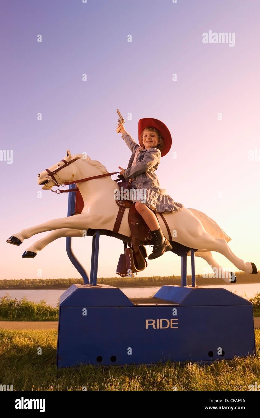 5 años de edad, niña vestido con traje occidental sentado en amusement pony ride, Canadá. Imagen De Stock