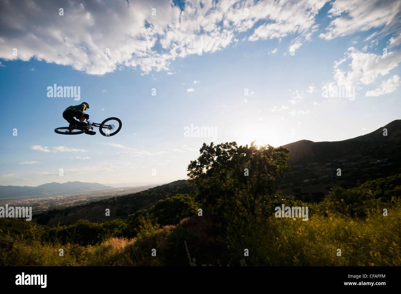 Ciclista de montaña saltando en Hillside Foto de stock