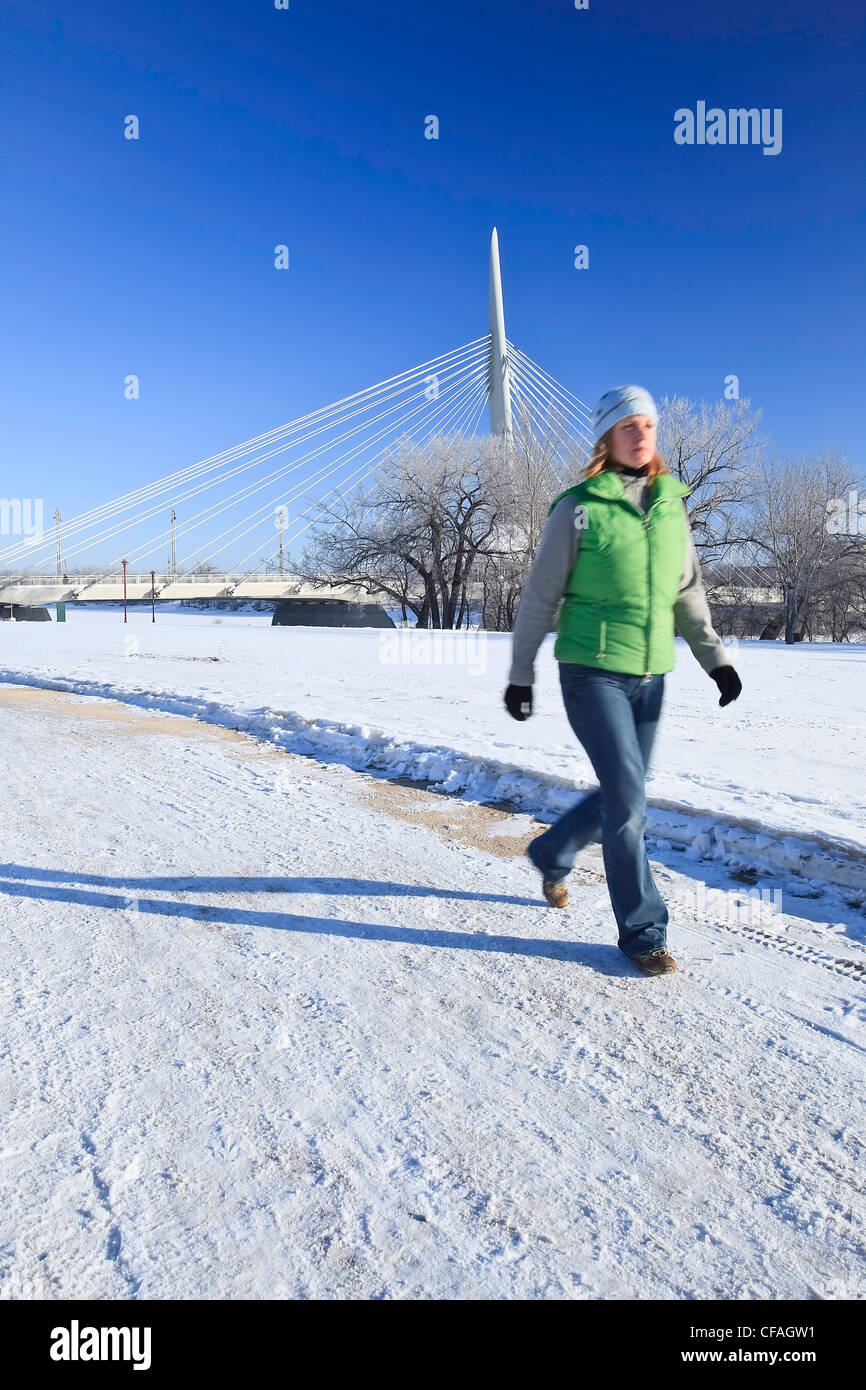 Movimiento de la imagen borrosa de una mujer caminando en invierno. Esplanade Arador Bridge en segundo plano. Las horquillas, Winnipeg, Manitoba, Canadá. Foto de stock