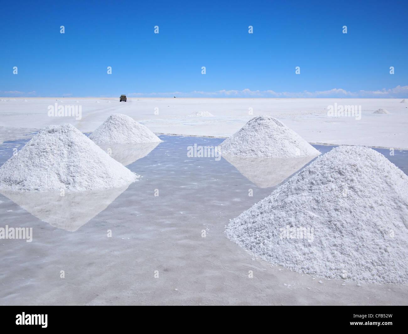 Secado de los montones de sal y el reflejo en el agua en el Salar de Uyuni (salinas) en Bolivia. Imagen De Stock