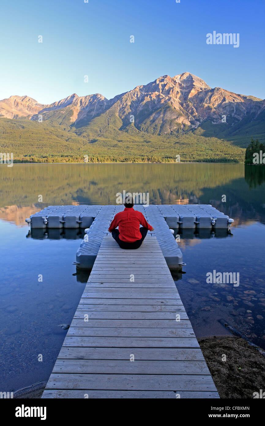 Varón de mediana edad meditando sobre dock en Pyramid Lake, el Parque Nacional de Jasper, Alberta, Canadá.Foto de stock
