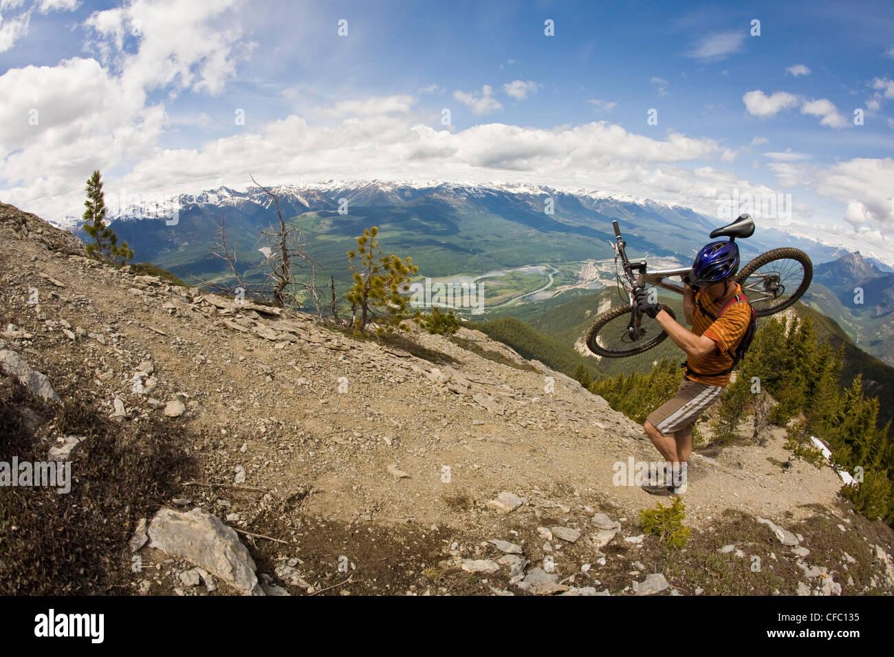 Un varón de mediana edad lleva su bicicleta de montaña de Mt. Siete para un épico descenso. Golden, Imagen De Stock