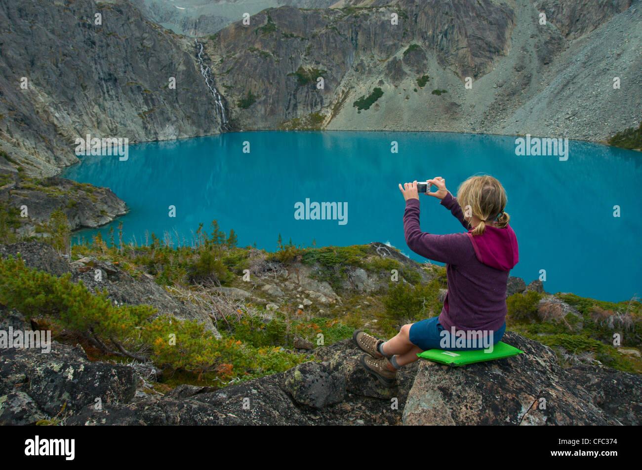 Una joven mujer ajusta una foto de una cascada y un lago azul con una cámara de apuntar y disparar, British Imagen De Stock
