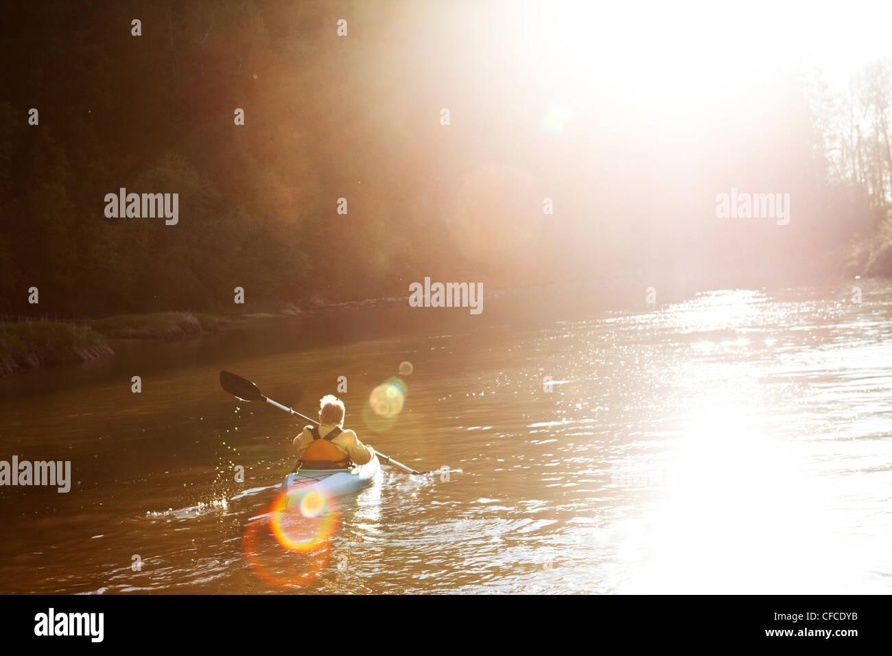Un aventurero mujeres jubilados kayaking abajo un gran río al atardecer en Idaho. Imagen De Stock