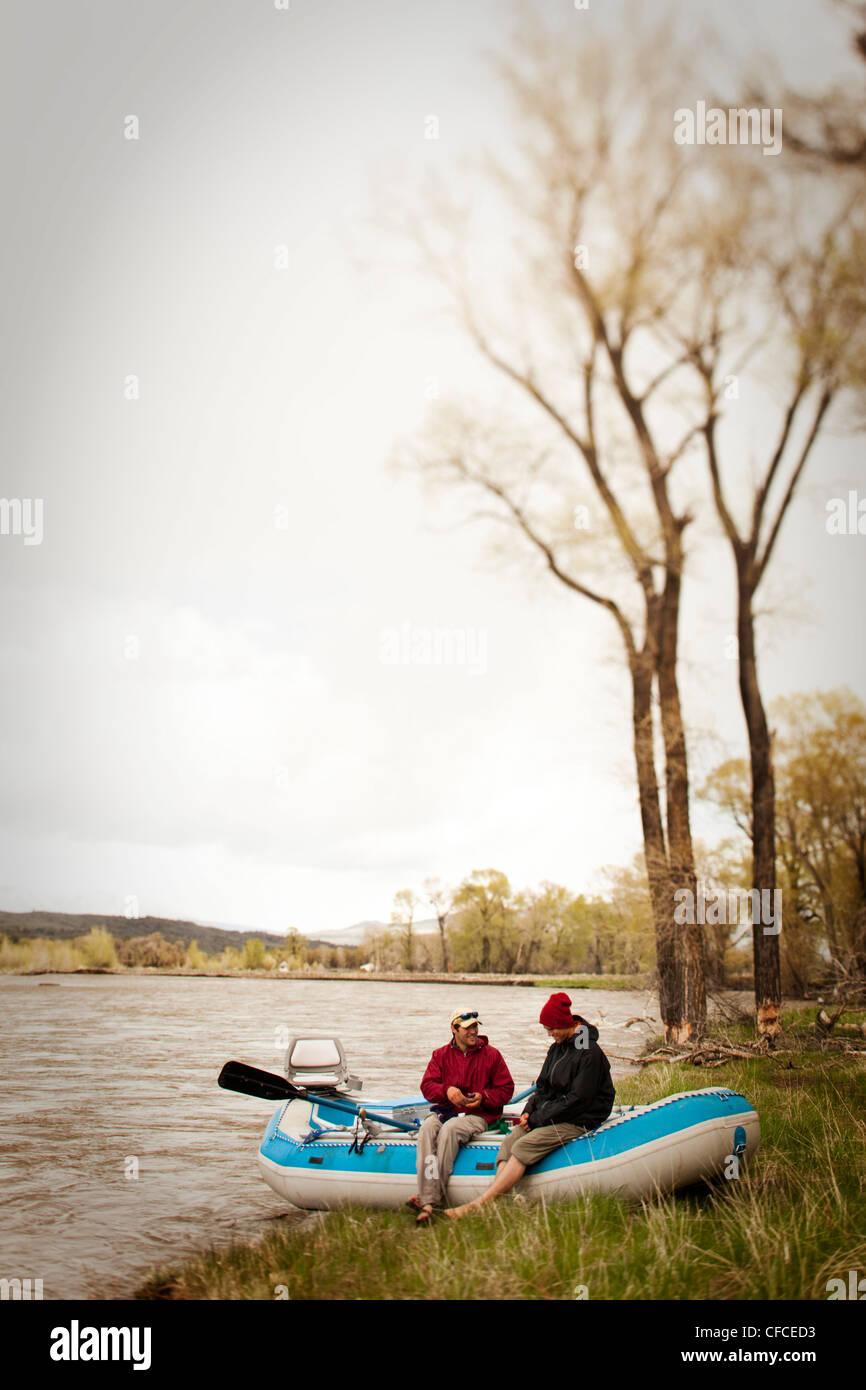 Dos hombres sonrisa mientras está sentado allí balsa en Montana. Imagen De Stock